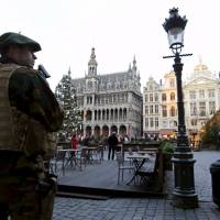 A Belgian soldier patrols on Brussels' Grand PlaceWednesday after two people were arrested in Belgium on Sunday and Monday, both suspected of plotting an attack in Brussels on New Year's Eve, federal prosecutors said. | REUTERS