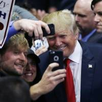 Republican presidential candidate Donald Trump stands with supporters after a campaign rally in Grand Rapids, Michigan, last Monday. | AP