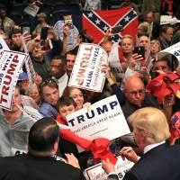 Republican presidential candidate Donald Trump works the crowd at the conclusion of his second campaign visit to Georgia at the Macon Centreplex Coliseum while a member of the crowd holds up the former flag of the state on Monday in Macon. | CURTIS COMPTON / ATLANTA JOURNAL-CONSTITUTION VIA AP
