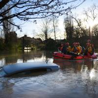 Members of the emergency services paddle down Huntington Road past a submerged parked car after the adjacent River Foss burst it's banks in York, northern England, on Sunday. Britain's government was holding emergency talks Sunday as flooding in northern England forced hundreds of people to leave their homes, including in the historic tourist destination of York. | AFP-JIJI
