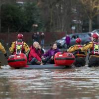 Members of the emergency services transport residents to safety after their homes were affected by floodwaters by the adjacent River Foss bursting its banks in York, northern England, on Sunday. | AFP-JIJI