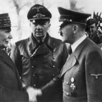 French Marshall Philippe Petain shakes hands with German Chancellor Adolf Hitler in occupied France on Oct. 24, 1940. Behind them is interpreter Paul Schmidt. At right is German Minister of Foreign Affairs Joachim von Ribbentrop. | AP