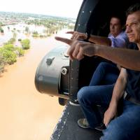 Argentine President Mauricio Macri (right) looks out of a helicopter during a flight over flood-hit areas in the city of Concordia, Entre Rios province, Sunday. | REUTERS/ARGENTINE PRESIDENCY/HANDOUT VIA REUTERS