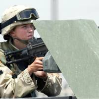 A female U.S. soldier manning a machine gun on a vehicle during clashes in the northern Iraqi city of Mosul in 2003. U.S. Defense Secretary Ash Carter said Thursday he is ordering the U.S. military to open up all positions — including combat roles — to women. | AFP-JIJI
