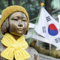 A statue of a girl representing sexual victims of the Japanese military stands in front of the Japanese Embassy in Seoul on Monday. | REUTERS