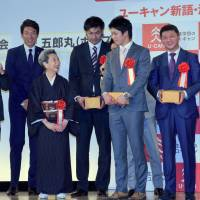 People associated with buzzwords of the year collect their prizes at an awards ceremony in Tokyo on Tuesday. | SATOKO KAWASAKI