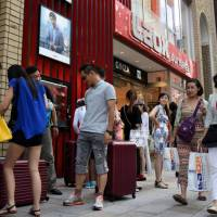 Chinese tourists exit from the home appliance retailer Laox Co.'s outlet in the Ginza district of Tokyo with shopping bags and suitcases on Friday. A favorable exchange rate and relaxed visa rules lured many Chinese to Japan this year. | SATOKO KAWASAKI
