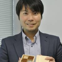 Keiichi Yoshino, 34, chief executive officer of Dari K Co., shows a product in Tokyo on Dec. 4. His firm operates chocolate shops in Kyoto featuring Indonesian cocoa. | KYODO
