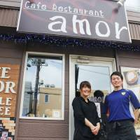 Haruyuki Ogawa, a former soccer player with an Argentine professional club, and his wife, Namiko, stand in front of their cafe in Sapporo on Oct. 2. | KYODO