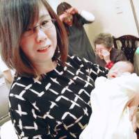 Chinami Hoshi of Dai-ichi Life Insurance Co. holds her grandchild recently in Matsudo, Chiba Prefecture. | KYODO