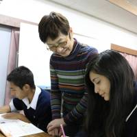 Yachiko Kawamura (center) teaches Keiko Ribera (right) at an after-school class in the city of Toyohashi, Aichi Prefecture. | CHUNICHI SHIMBUN