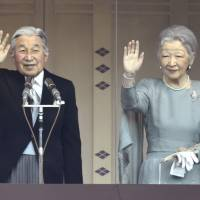 Emperor Akihito and Empress Michiko greet well-wishers on the occasion of the Emperor's 82nd birthday, at the Chowa-den Hall of the Imperial Place in Tokyo on Wednesday. Members of the public gathered outside to wave to the couple, who stood behind bulletproof glass. | KYODO