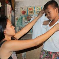 Kean Geronimo, a 7-year-old elementary school boy with a heart defect, puts on a shirt with his mother's help at their home in Manila. | ERDA FOUNDATION
