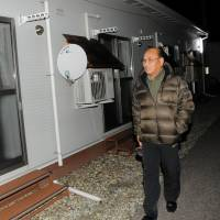 Masanori Takeuchi, who heads a neighborhood council at a temporary housing facility in Aizuwakamatsu, Fukushima Prefecture, patrols vacant units at night. | FUKUSHIMA MINPO