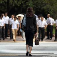 A lone woman waits to cross a street in Tokyo. A government advisory panel on gender equality submitted a report Tuesday urging the nation to change the male-oriented work culture. | BLOOMBERG
