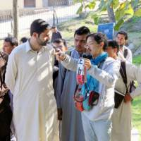 Atsushi Noguchi (center) from the Japanese Center for South Asian Cultural Heritage teaches students of Hazara University how to take photos of historical monuments with digital cameras in Mansehra, northern Pakistan, on Oct. 30. The center and the university are working together to preserve ancient Buddhist monuments using 3-D imaging technology. | KYODO