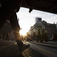 Morning commuters walk across a pedestrian crossing in Tokyo on Dec. 10. Once people fall into the wrong side of the country's rigid labor system, it is harder to get a traditional job-for-life. | BLOOMBERG