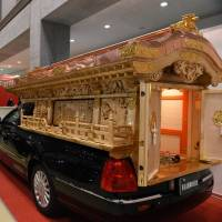 A hearse decorated with a traditional shrine is displayed at the Life Ending Industry Expo in Tokyo on Tuesday. | AFP-JIJI