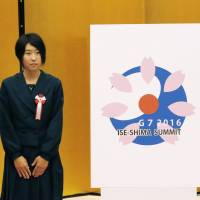 During a ceremony at the prime minister's office Monday, Shiho Utsumiya, 18, stands next to her logo design for next year's Group of Seven summit in the Ise-Shima area in Mie Prefecture. | KYODO