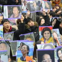 People gather in front of the Japanese Embassy in Seoul with photographs of late 'comfort women' on Wednesday. The Korean Council for Women Drafted for Sexual Slavery by Japan said the same day it plans to start a movement to erect both inside and outside the country statues similar to the one located in front of the embassy. | KYODO