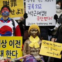 Protesters on Wednesday stand by a statue symbolizing the girls and young women forced into servitude as military 'comfort women.' A rally takes place every week in front of the Japanese Embassy in Seoul. | REUTERS