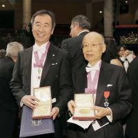 Nobel Prize winners Takaaki Kajita (left) and Satoshi Omura show their medals Thursday after the award ceremony in Stockholm. | KYODO