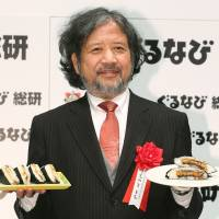 Tochi Ueyama, author of the 'Cooking Papa' manga series, holds dishes of onigirazu in Tokyo on Monday as the Gurunavi Research Institute chose the innovative take on the traditional onigiri rice ball as the dish of the year for 2015. | KYODO