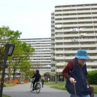 An elderly woman walks by the sprawling Takashimadaira apartment complex in Itabashi Ward, Tokyo, in April 2014. | KYODO