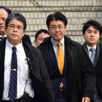 Sankei Shimbun journalist Tatsuya Kato (in yellow tie) arrives for trial at a court in Seoul on Thursday. | AFP-JIJI
