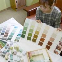 A Sapporo municipal employee shows 70 colors the city has chosen as the best matches for its landscape. | KYODO