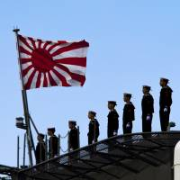 Sailors line the deck of the helicopter destroyer Izumo as the flat-top departs the Japan United Marine shipyard in Yokohama on March 25. | REUTERS