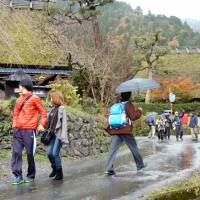 Tourists stroll in the rain through the increasingly popular Kayabuki no Sato village of traditional thatched-roof houses in Miyama, northern Kyoto, on Dec. 1. | KYODO