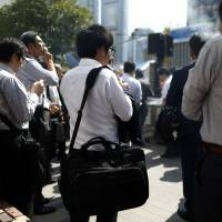 People smoke cigarettes outside a train station in Tokyo on Sept. 28. | BLOOMBERG