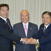 Sports and education minister Hiroshi Hase (left), Tokyo Gov. Yoichi Masuzoe (center) and Olympics minister Toshiaki Endo demonstrate their solidarity for the cameras Tuesday after striking a cost-sharing deal on the main stadium for the 2020 Olympics. | KYODO