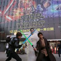 Men wielding lightsabers strike a pose with a woman dressed as Princess Leia in front of Toho Cinemas' Roppongi Hills theater in Tokyo's Minato Ward on Friday ahead of the premiere of 'Star Wars: The Force Awakens.' | RIE ISHII
