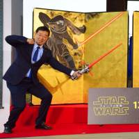 Kenji Yamada (left), governor of Kyoto Prefecture, embraces the Dark Side as artist Taro Yamamoto holds 'Star Wars' droid BB-8.   KYODO
