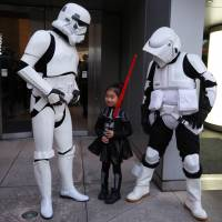 A girl poses between Stormtroopers at Toho Cinemas' Roppongi Hills theater in Tokyo's Minato Ward on Friday ahead of the first showing of the seventh movie in the 'Star Wars' franchise. | RIE ISHII