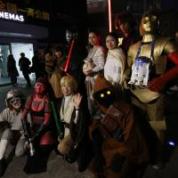 """Star Wars"" fans strike a pose Friday at Toho Cinemas' Roppongi Hills theater in Minato Ward, Tokyo, ahead of the first screening of ""The Force Awakens."" 