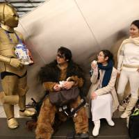 'Star Wars' fans take a break outside Toho Cinemas' Roppongi Hills theater in Minato Ward, Tokyo, on Friday ahead of the first showing of 'The Force Awakens.' | RIE ISHII