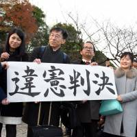 Supporters of a lawsuit challenging a six-month ban on remarriage for female divorcees hold a banner reading 'Unconstitutional ruling' after the Supreme court's decision. | SATOKO KAWASAKI