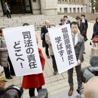 Lawyers and opponents of restarting the Takahama nuclear plant in Fukui Prefecture protest the ruling outside the court in Fukui on Thursday. The banners read: 'Where is the responsibility of the justice system?' and 'Nothing learned from the Fukushima nuclear disaster.' | KYODO