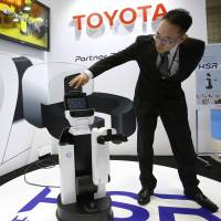 Akifumi Tamaoki, general manager of Toyota's 'partner robot' division, speaks with the HSR robot at the International Robot exhibition in Tokyo on Wednesday. | AP