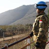 A U.N. peacekeeper of the United Nations Interim Force in Lebanon (UNIFIL) stands at a lookout point in Adaisseh village near the Lebanese-Israeli border, southern Lebanon December 21, 2015. | REUTERS