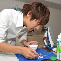 Out, damned spot: Laundry expert Yuichi Nakamura demonstrates how to clean a stain with a toothbrush at his studio in Kagurazaka, Tokyo, on Nov. 25. | YOSHIAKI MIURA