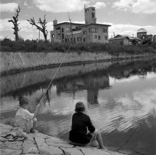 Two young boys fish in the shadow the Atomic Bomb Dome in Hiroshima in 1946. On her father's photo, Valerie Neale writes: 'At ground zero, almost exactly one year after the day of the bomb, surely anything found in the river would have been contaminated, but the Japanese people and the BCOF troops would not have known this.' | DERRICK WOOLLACOTT