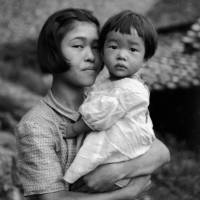 An untitled image of a young woman and a child conveys a mix of curiosity and wariness. Valerie Neale, one of Woollacott's two daughters, says this is one of her favorites. | DERRICK WOOLLACOTT