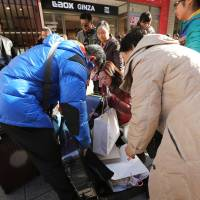 No room at the inns: Chinese shoppers pack purchases into a suitcase in Tokyo's ritzy Ginza district. More and more tourists are coming to Japan on shopping trips, and some have been opting to stay in rented-out residential apartments instead of hotels, sometimes straining relations with the locals. | BLOOMBERG