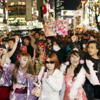 Out of the shadows: Kyaba-kura hostesses and other assorted nightspot workers hold a rally in 2010 through the Kabuki-cho entertainment district in Shinjuku, calling for better work conditions, among other issues. | KYODO