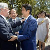Now, I am the master: Thomas Johnson greets his former student Japanese Prime Minister Shinzo Abe as University of Southern California President C.L. Max Nikias and Akie Abe look on. | GUS RUELAS