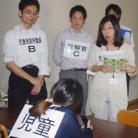 Police and local government workers in Kasugai, Aichi Prefecture, train in how to deal with child abuse using role-play. | KYODO